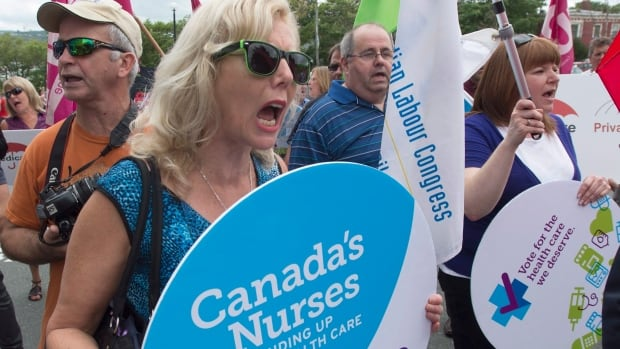 Health care protesters march outside the hotel at the summer meeting of Canada's premiers in St. John's last week. A new report by the federal budget watchdog comes than a week after the premiers urged Ottawa to boost federal health-care funding to cover at least 25 per cent of all health spending.