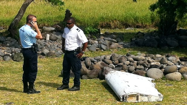A policeman and a gendarme stand next to a piece of debris, likely from an aircraft, found on the northeast coast of Réunion Island in the French Indian Ocean on Wednesday. The source of the debris has not been determined but there was speculation online that it could be part of the missing Malyasia Airlines Flight MH370.