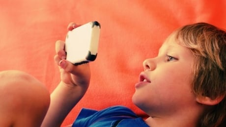 Child looks at mobile phone