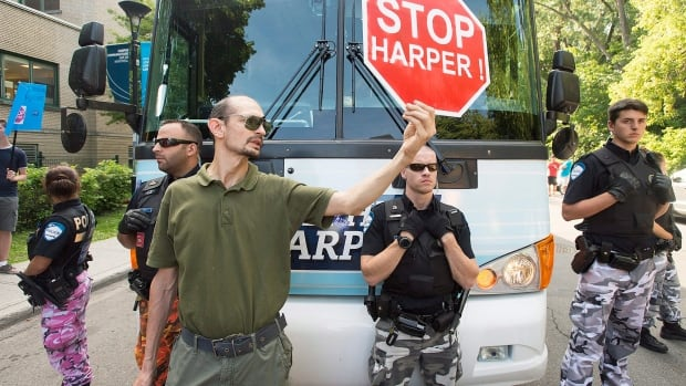 An anti-Stephen Harper protester blocks the party's campaign bus during a Conservative party federal election rally on Sunday.