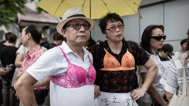 Hundreds of protesters brought bras to Hong Kong's police headquarters in support of a woman who was sentenced to three-and-a-half months jail for using her breast to bump a police officer.