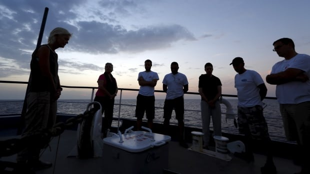 Crew members on the Migrant Offshore Aid Station ship MV Phoenix pause for a moment of reflection at dusk during a search for missing migrants after their boat capsized off the coast of Libya.