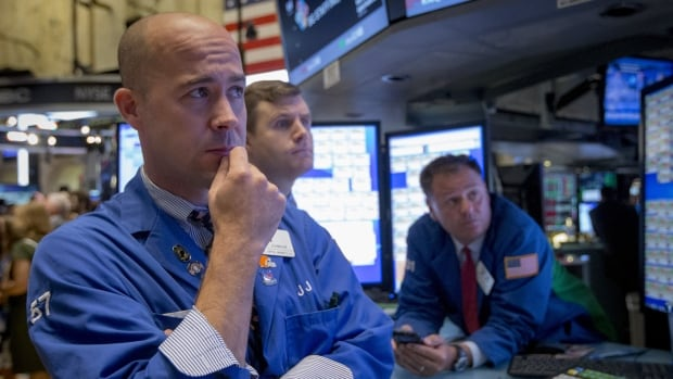 Traders work on the floor of the New York Stock Exchange on Tuesday. U.S. stocks fell in early trading in a broad-based retreat as China's surprise devaluation of the yuan pushed the dollar higher and pressured commodity-related shares.