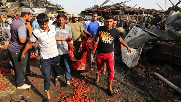 People evacuate the body of a victim killed in a bombing at Baghdad's Jameela market on Aug. 13. A massive truck bomb ripped through the popular food market in a predominantly Shiite neighbourhood, killing at 58.