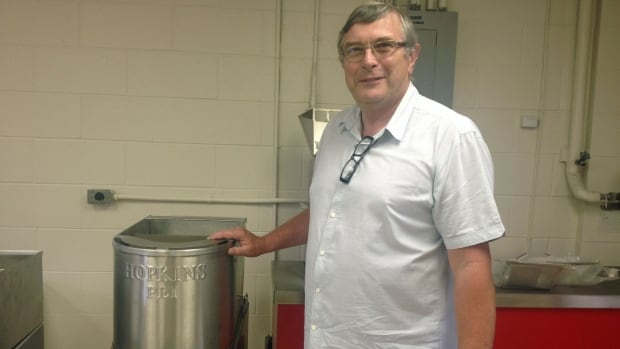 Hopkins CEO Chris Hopkins with one of companies first french fry cutters manufactured on P.E.I.