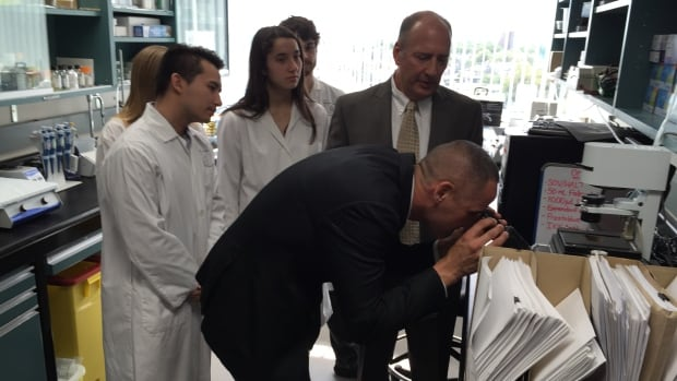 Kevin chief peers through microscope as Dr Benedict supervises.