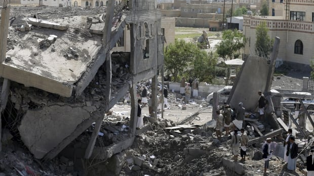 Houthi militants gather on the rubble of the offices of the education ministry's workers union, destroyed by Saudi-led air strikes, in Yemen's northwestern city of Amran on Wednesday. A Saudi-led Arab coalition has been bombarding the Iranian-allied Houthi rebel movement - Yemen's dominant force - since late March.