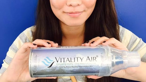 Vitality Air model, Hannah Lam, holds a can filled with air that the compay says was collected directly from Banff, Alta.