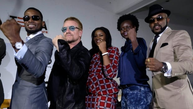 Bono, second left, poses with African music stars after a press conference in Lagos, Nigeria, Friday, Aug. 28, 2015.