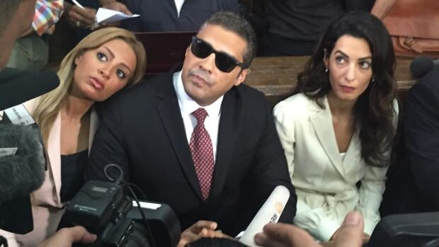 Canadian journalist Mohamed Fahmy was in a Cairo court with his wife Marwa and human rights lawyer Amal Clooney on Aug. 30 as he awaited his retrial verdict.  The judge sentenced him and two fellow Al-Jazeera journalists to three years in prison.