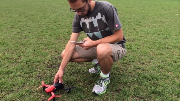 Brennan Jones checks on his drone, which he's using to test the usefulness of video-conferencing with the flying machine.
