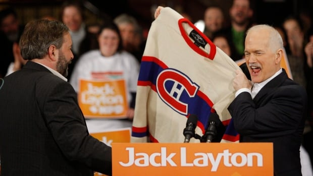 Jack Layton holds up a old-style Montreal Canadiens jersey given to him by then candidate Tom Mulcair in Montreal in April 2011.
