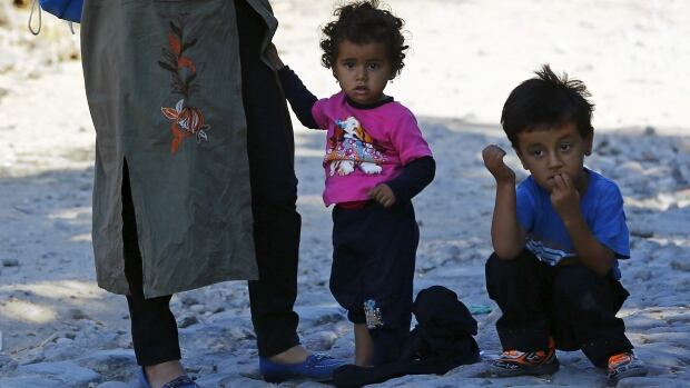 A Syrian woman and her children pause as they walk to the shore in the Turkish coastal town of Behramkale to board a dinghy bound for the Greek island of Lesbos.