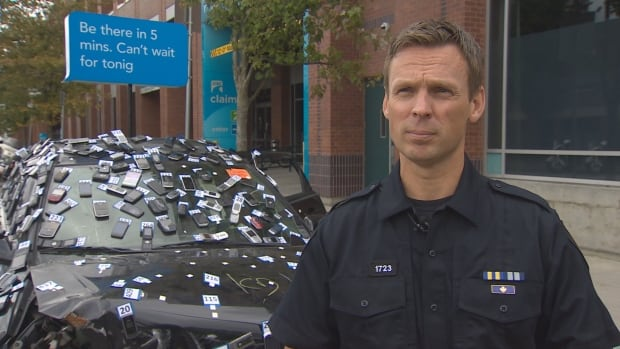 Const. Brian Montague of the Vancouver Police Department stands in front a crashed car which has 437 cellphones on it - representing the number of deaths on B.C. roads due to distracted driving between 2009 and 2013.