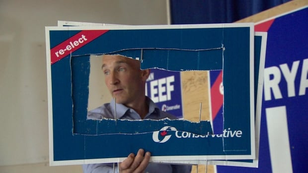 Yukon Conservative candidate Ryan Leef holds up damaged campaign signs. Leef made a citizen's arrest on a woman Aug. 27 after he caught her cutting holes in the signs on a highway outside Whitehorse.