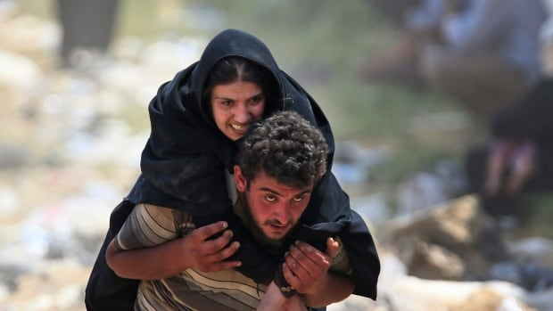 A Syrian refugee carries a sick woman on his back in Akcakale, southeastern Turkey, as they flee intense fighting in northern Syria between Kurdish fighters and Islamic State militants. The PMO had asked for an audit of Syrian refugee cases, temporarily halting their processing.