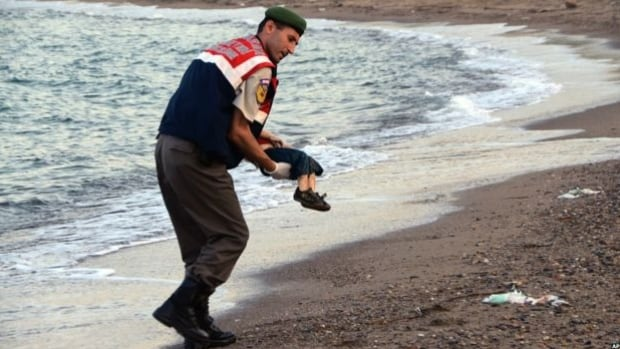 A Turkish police officer carries the lifeless body of Alan Kurdi, one of a dozen Syrian refugees who drowned off the coastal town of Bodrum, Turkey.