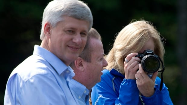 Conservative Leader Stephen Harper looks towards the media as his wife takes a photo of the cameras on hand for a photo op in North Bay, Ont.
