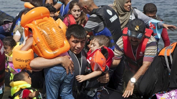A Syrian refugee, left, carries two children after arriving on a dinghy on the Greek island of Lesbos, September 7, 2015. Greece is struggling to cope with the hundreds of migrants and refugees from the war in Syria making the short crossing every day from Turkey to Greece's eastern islands, including Kos, Lesbos, Samos and Agathonisi.