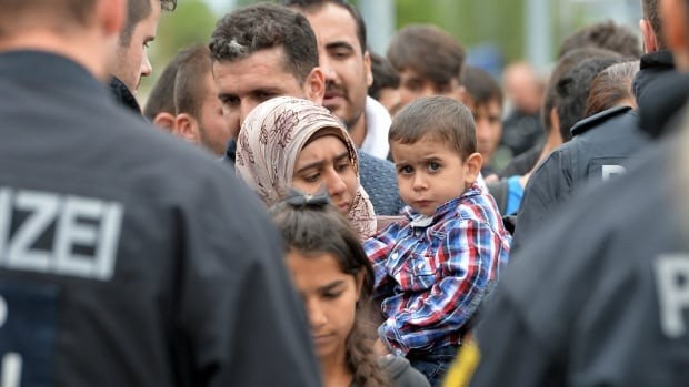 German police register refugees at the rail station in Freilassing, Germany, on Monday before taking them away in buses. Germany introduced temporary border controls Sunday to stem the tide of thousands of refugees streaming across its frontier.