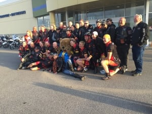 The cyclists pose with their police escort and the motor cycle club that escorted them through Regina. (Lauren Golosky/CBC)
