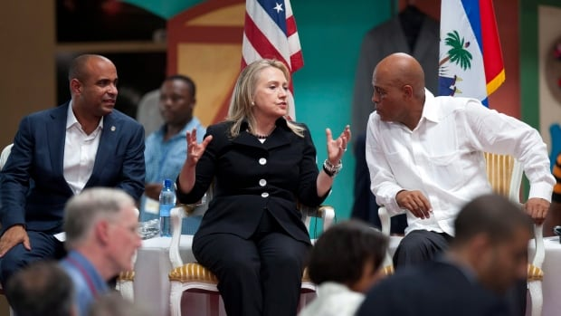 Then secretary of state Hillary Clinton, centre, speaks to Haitian President Michel Martelly, right, during the inauguration of the Caracol Industrial Park in 2012. Clinton encouraged foreigners to invest in Haiti but a Canadian researcher is questioning who really benefited from the economic intervention.