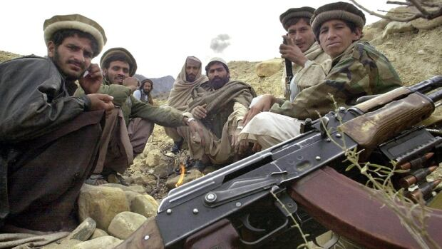 Afghan mujahideen keep warm before a fire beside their Kalashnikov rifles. December 2001.