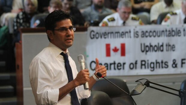 Ontario Public Safety Minister Yasir Naqvi, with former Hamilton police chief Glenn De Caire in the background, spoke at a consultation in September about controversial street checks.