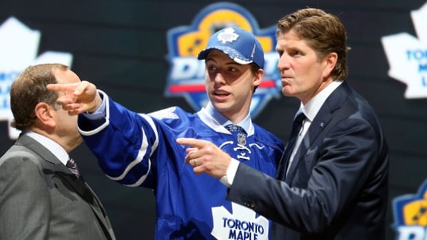 Mike Babcock, right, talks with Mitchell Marner, middle, after Marner was selected fourth overall by the Toronto Maple Leafs in the first round of the 2015 on June 26 in Sunrise, Fla.