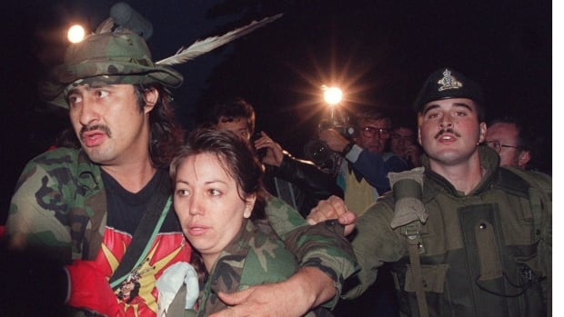 Mohawk Warrior known as Noreiga clutches an unidentified woman as he is taken into custody Sept. 26, 1990 by Canadian soldiers after 78 days defending their land.
