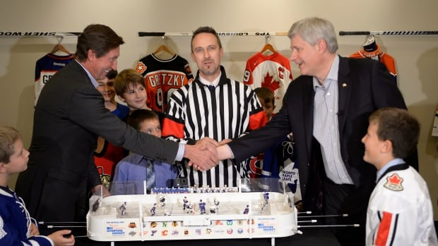 Conservative Leader Stephen Harper shakes hands with Wayne Gretzky before a table-top hockey game during a campaign event in Toronto on Friday. Social media users are divided over Gretzky's endorsement of Harper.