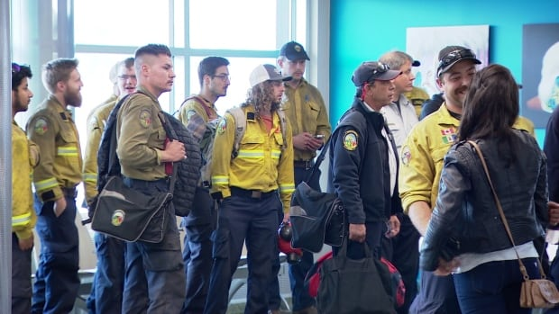 Yukon firefighters file into the Whitehorse airport Friday after nearly two months of battling wildfires in the northwest U.S.