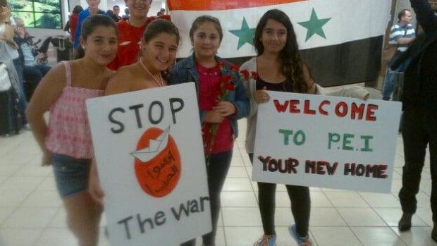 Members of P.E.I. Syrian community hold signs at the airport as they away the arrival of Awak Alkhalil and his family on Friday night.
