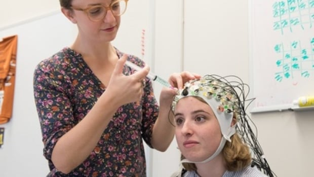 Sophia Van Hees prepares the electroencephalography cap to monitor the electrical activity in the brain of a study participant.