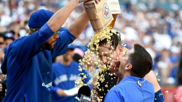 Toronto Blue Jays pitcher David Price pours popcorn over the head of third baseman Josh Donaldson on Sept. 27, 2015.