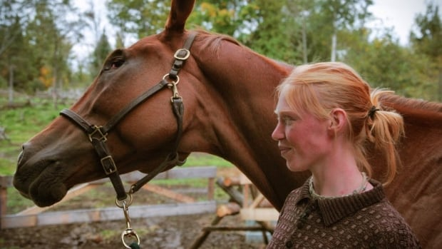 Rusty the horse poses with trainer Hilary Popiel at her stable in Carleton Place, Ont., near Ottawa. Rusty lost an eye three years ago at a horse race in Boston.