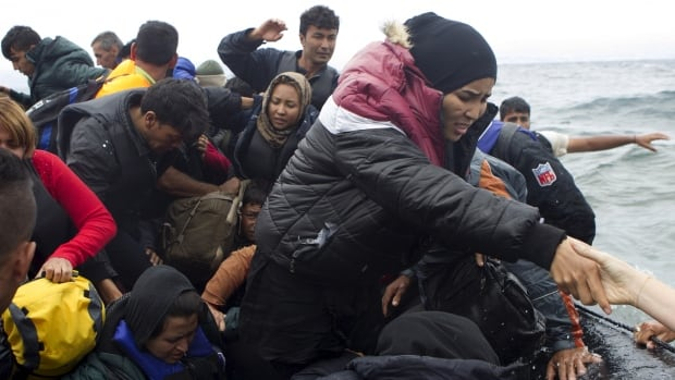Refugees and migrants struggle to get off an overcrowded dinghy as they arrive on the Greek island of Lesbos, after crossing a part of the Aegean Sea from the Turkish coast on Wednesday. At least 430,000 refugees and migrants, a record number, have taken boats across the Mediterranean to Europe this year, according to International Organization for Migration figures.