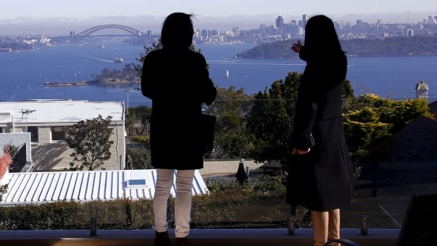 A real estate agent escorts a potential buyer from Shanghai around a property in Sydney, Australia. The city has the same housing affordability problems as markets such as Toronto or Vancouver.