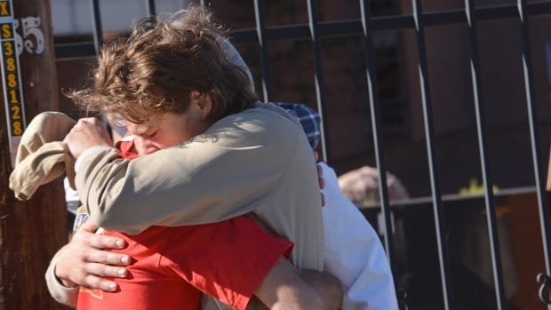 Two people embrace outside a Northern Arizona University student dormitory, Friday in Flagstaff, Ariz., after an early morning confrontation between two groups of students escalated into gunfire.