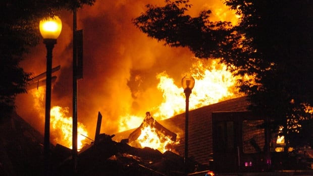 A fully engulfed fire burns on Independence Avenue near Prospect in Kansas City, Mo., on Monday.