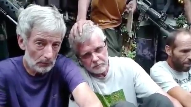 The RCMP are investigating the beheading of Canadian John Ridsdel (middle), shown here in a still image from a Abu Sayyaf hostage video. Canadian Robert Hall, left, remains in captivity with Norwegian Kjartan Sekkingstad right.