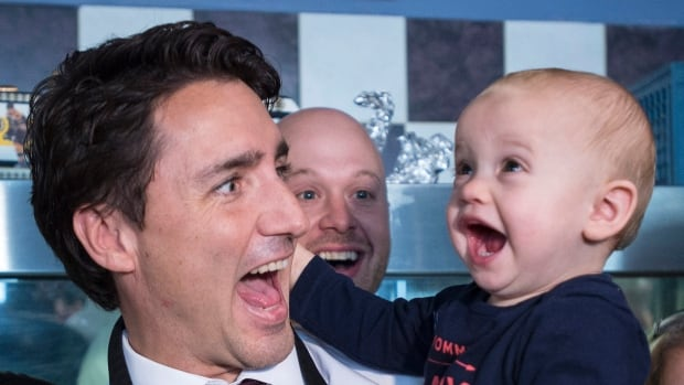 Liberal Leader Justin Trudeau makes a funny face with a young child during a campaign stop at a restaurant, Wednesday, October 14, 2015 in Welland, Ont.