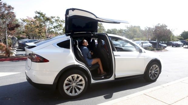 A Tesla Model X picks up passengers during a Tesla event in Palo Alto, Calif., in this October 2015 file photo. Some Tesla Motors vehicles can park themselves without a driver inside with a software update beamed to customers over the weekend.