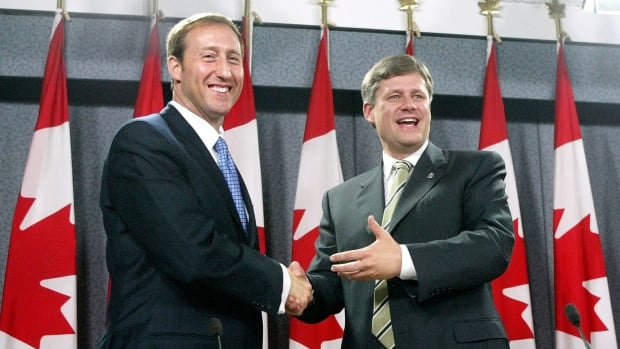 In October 2003, Progressive Conservative leader Peter MacKay shakes hands with Canadian Alliance leader Stephen Harper after their announcement of a party merger.