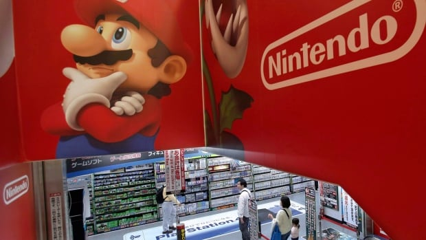 Shoppers walk under the logo of Nintendo and Super Mario characters at an electronics store in Tokyo on May 7, 2014. According to reports, the next Nintendo system, code named the NX, will be a hybrid of the traditional home console and portable handheld formats.