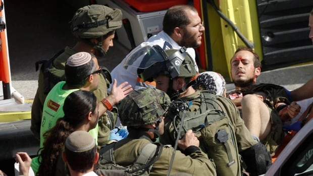 A wounded Israeli soldier is carried into an ambulance after he was stabbed in Hebron by a Palestinian man wearing a yellow 'press' vest and T-shirt identifying him as a journalist.