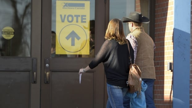 Jody, Jason Wilson and three-year-old Riley head to the polls in Nanton, Alberta, during the country's 42nd general election today.