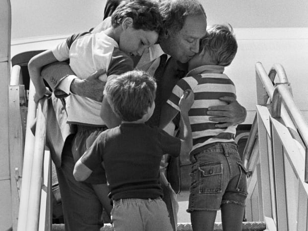 Justin, 9 (left), Michel, 5 (centre), and Sacha, 7, welcome their father home from his European trip on June 27, 1981.