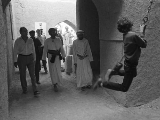 Justin, 11, swings on a chain as his father watches during a tour of an old fort in the Omani town of Nizwa Dec. 2, 1983.  Pierre and Justin Trudeau spent the day visiting the towns of Jebel and Nizwa, 165 kilometres south of Muscat.