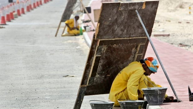 An Asian laborer avoids the direct sun by working behind a wooden sign, as he works on a manhole alongside of an under construction road in Dubai, United Arab Emirates. Parts of the Persian Gulf by the end of the century will on occasion will be just too hot for the human body to tolerate, if carbon dioxide emissions continue on current trend, a new study says.